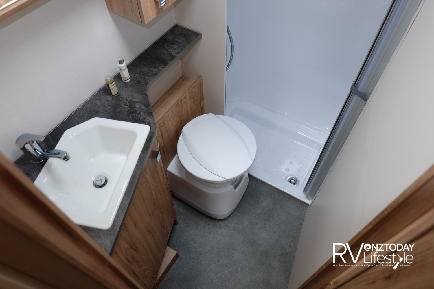 The bathroom is good size for such a compact vehicle. Sink/vanity unit with storage to the left, mirror and storage cabinets above, cassette toilet in the middle with shelf storage behind, separate shower stall to the right with pull-out concertina door