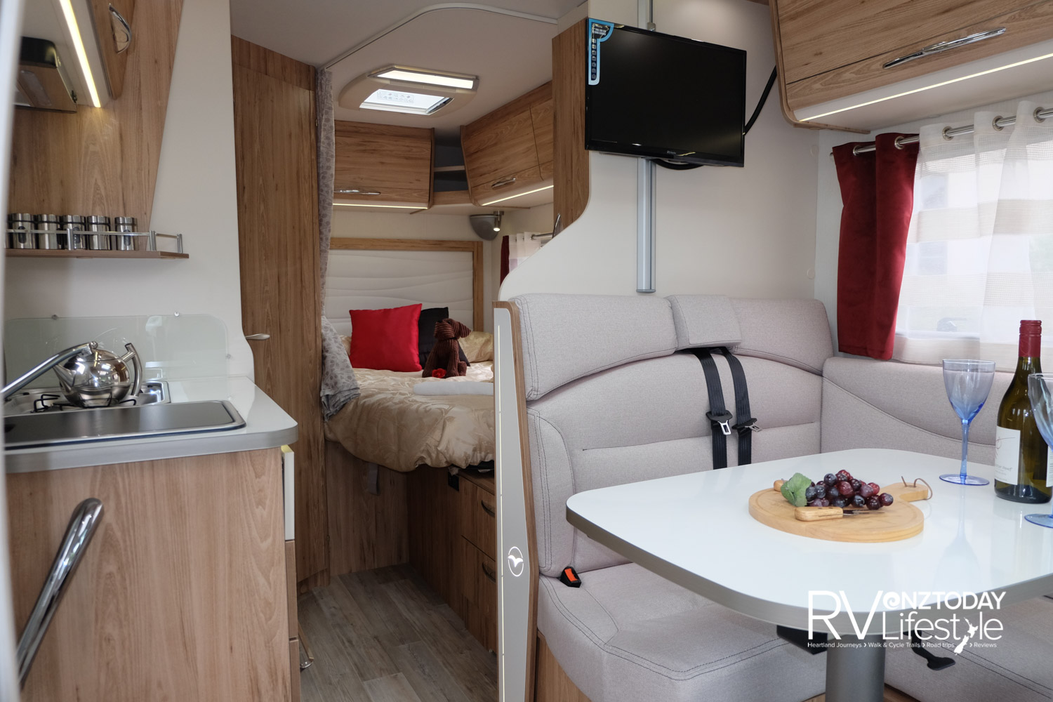 Seatbelts for two passengers, the TV is on a height-adjustable rail, overhead locker storage here and through to the bedroom area, with wardrobe between the spaces. Side and net curtains add a homely feel to the windows, though they have pull-up blinds and fly screens on all windows
