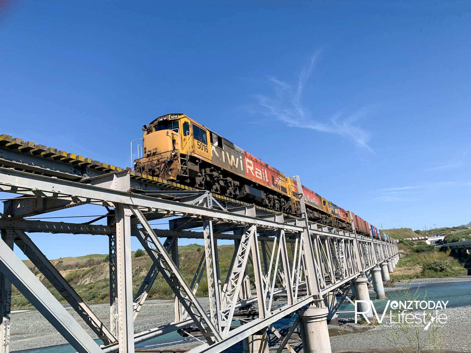 A long goods train rumbles its way across the old Seddon, double-decker bridge. The lower car deck has been removed