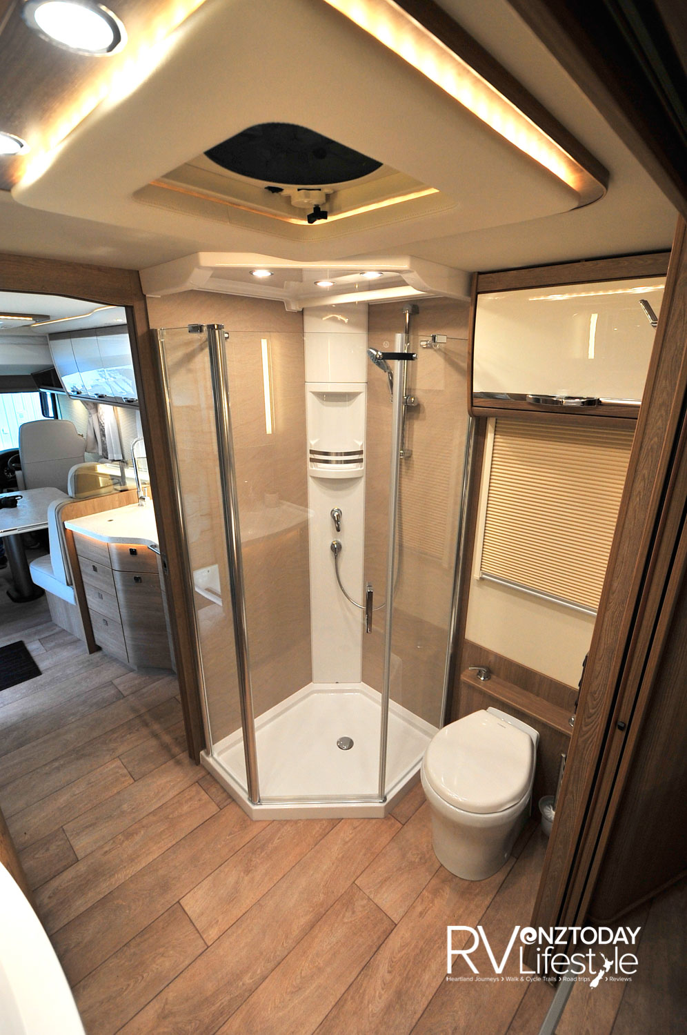 Toilet suite sits beside the large shower box, roof vent above, opening window, there is an extendable shower-top head behind the sink, for easy cleaning of the unit I presume