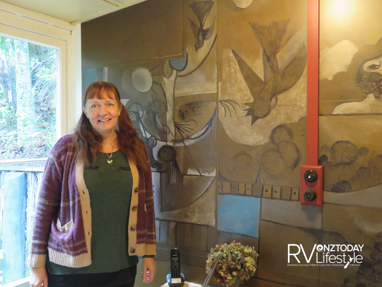 Volunteer Georgina Carlton beside a replica of McCahon's painting in the dining area