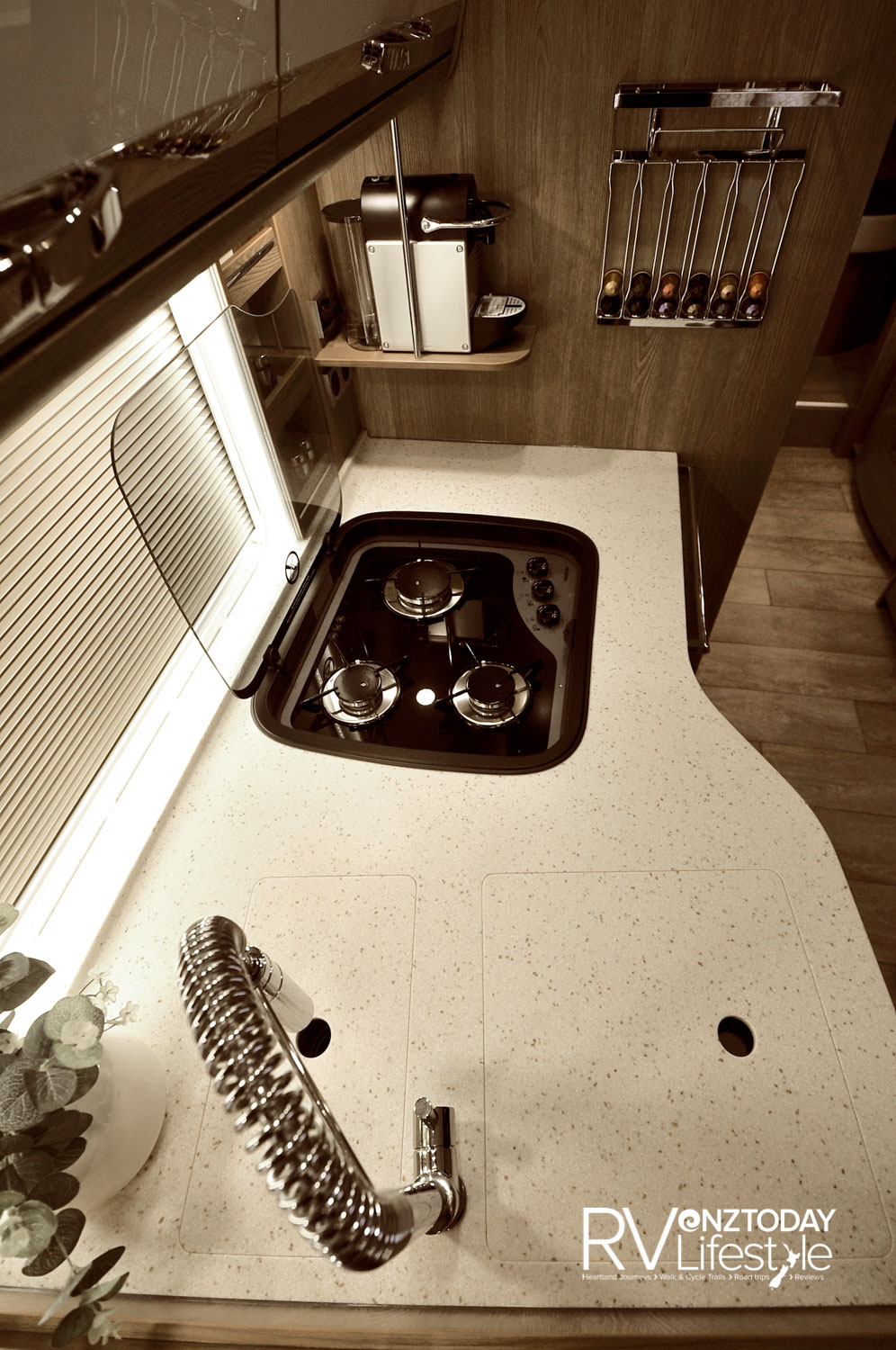Kitchen bench boasts two sinks, with covers, three-burner gas hob, with glass lid for bench space. Note the fitted coffee machine on the shelf