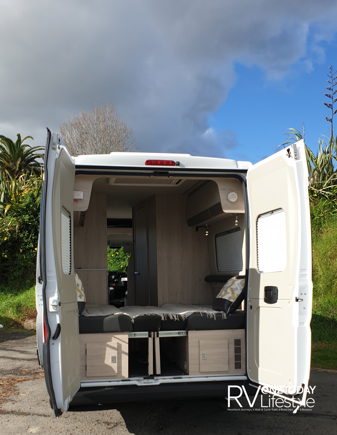 Rear doors open revealing rear lounge area made up to a large 1860mm x 1640mm full width bed. Step up on the back bumper to enter from the rear