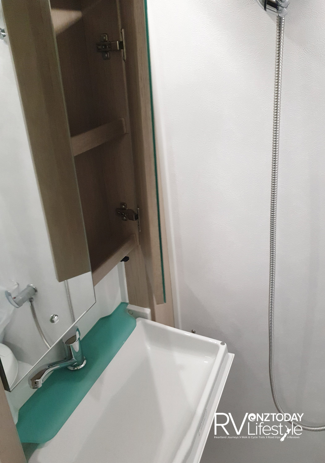 The bathroom. The door opens to a pedestal 12v electric flush cassette toilet with shower curtain, a nifty sink unit folds back into the wall for storage. Storage above and below.