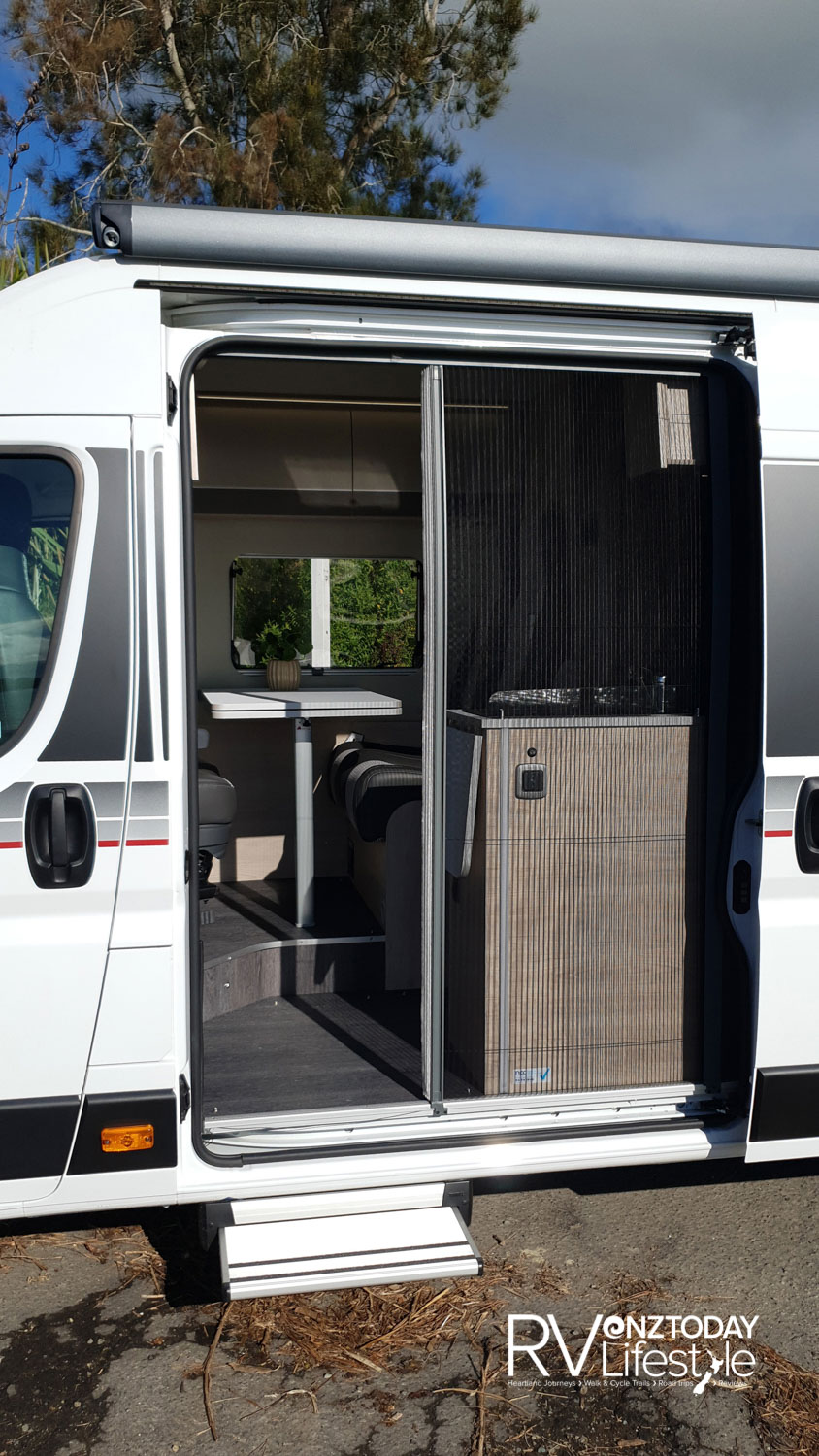 The sliding door opens, the electric step pops out as required, and a new feature for these types of vehicles - a pull-out full door-width fly screen. The wind-out awning is full body length above