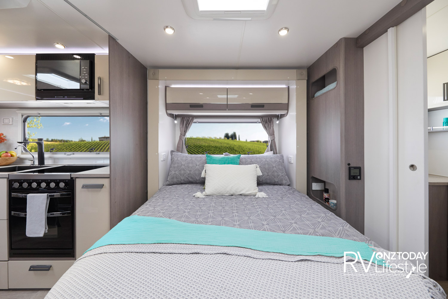 The bed is in the slide-out area, overhead storage and LED lights with a big window, light switches by the bedside, book and cup area, power points alongside. Rear bathroom sliding door