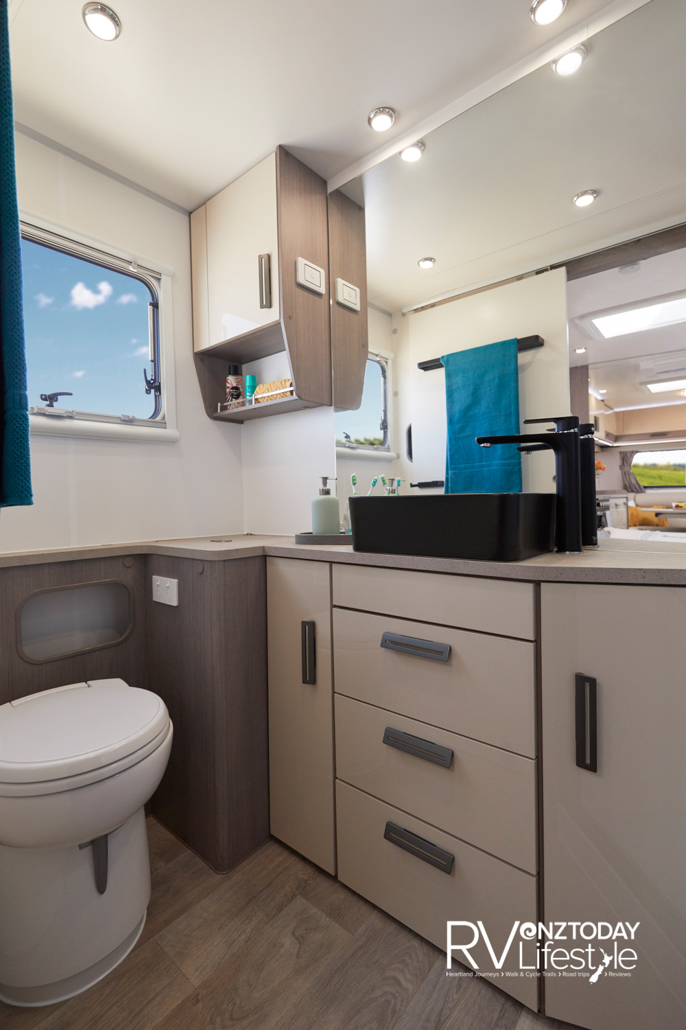 The full-width bathroom has plenty of space. 112v electric flush pedestal cassette toilet, drawers and cupboards under the long bench, in the left corner a laundry station - with washing machine in the cupboard. In the right corner out of sight a shower