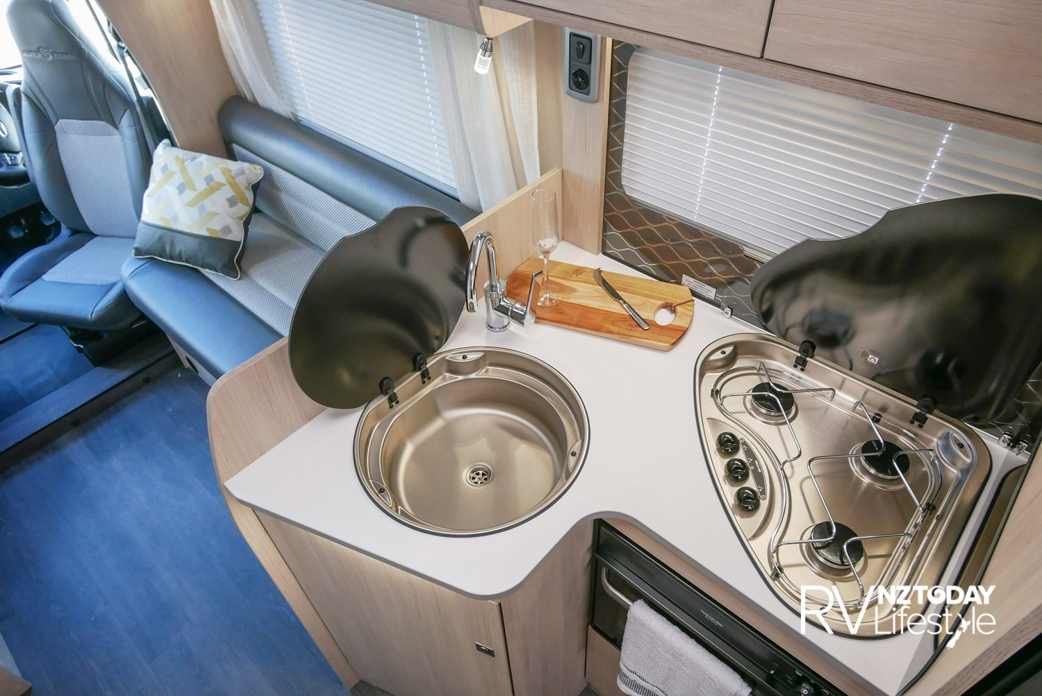 The kitchen area has a compact L-shaped bench, three-burner gas hob and the round stainless steel sink – both with glass lids for preparation space. An under-bench combined gas oven/grill, and under-sink storage cupboard with slide-out utility draw inside