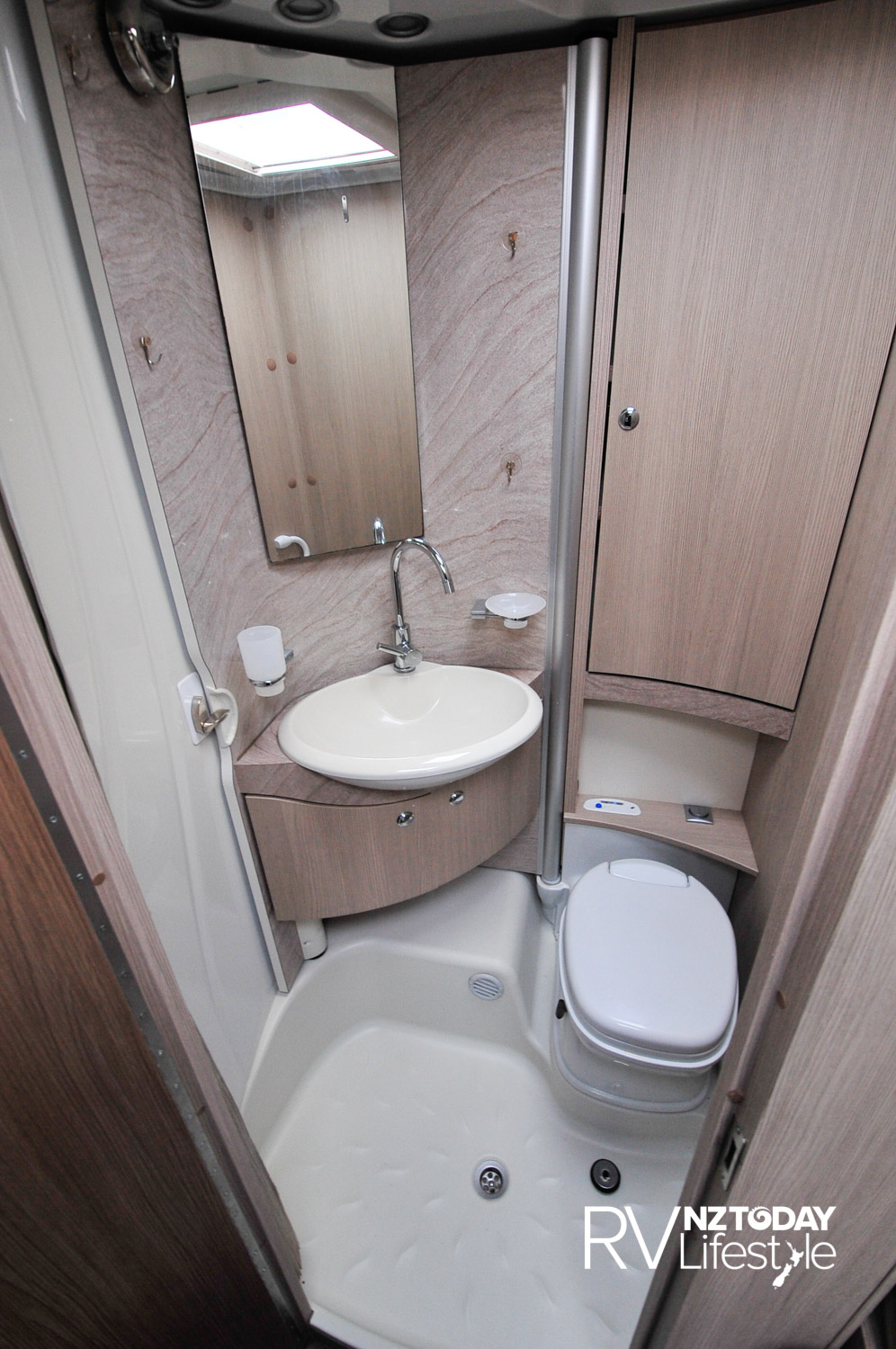 The bathroom has good storage behind the toilet, the lightswitch is behind the toilet as well. Vanity basin, mirror with side lights and above, storage underneath,, Clip on the left unclips