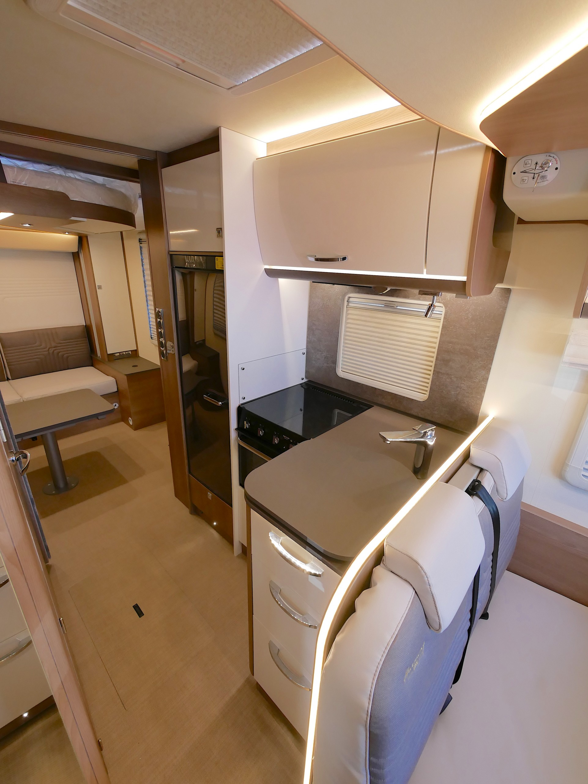 Compact L-shaped kitchen, overhead locker storage, LED strip lighting above and around cupboards and spotlights below