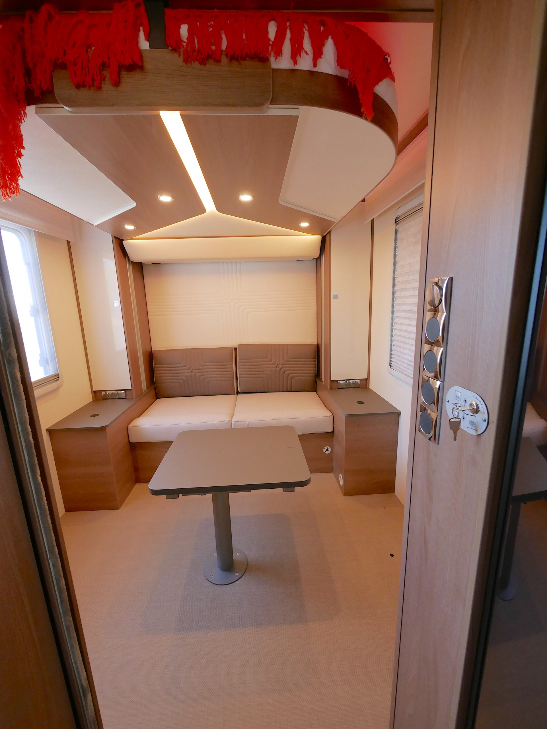 The rear lounge is different, a two-seater couch in the middle rear, adjustable and foldable table in front. Wardrobes and bench tops both sides